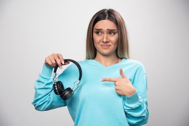 Blond meisje in blauw sweatshirt luistert naar de koptelefoon en geniet niet van de muziek.