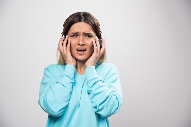 Blond meisje in blauw sweatshirt luistert naar de koptelefoon en geniet niet van de muziek