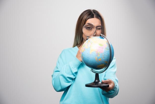 Blond meisje in blauw sweatshirt met een wereldbol en op zoek naar een bestemming met vergrootglas.