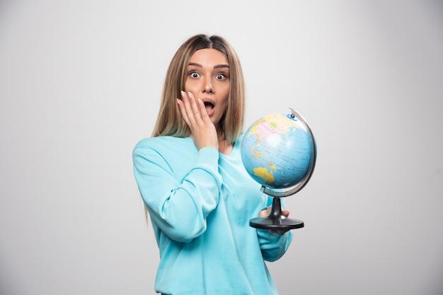 Blond meisje in blauw sweatshirt met een wereldbol en op zoek verrast