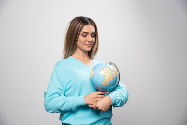 Blond meisje in blauw sweatshirt met een wereldbol, gissen locatie en plezier.