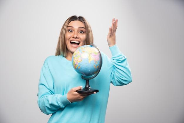 Blond meisje in blauw sweatshirt met een wereldbol, gissen locatie en plezier