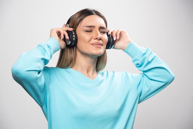 Blond meisje in blauw sweatshirt met koptelefoon, genietend van de muziek en plezier.