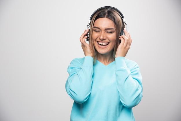 Blond meisje in blauw sweatshirt met koptelefoon, genietend van de muziek en plezier