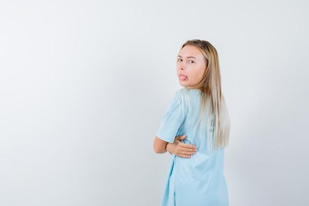 Blond meisje in blauw t-shirt dat zich omdraait, tong uitsteekt terwijl poseren en er mooi uitziet, vooraanzicht.