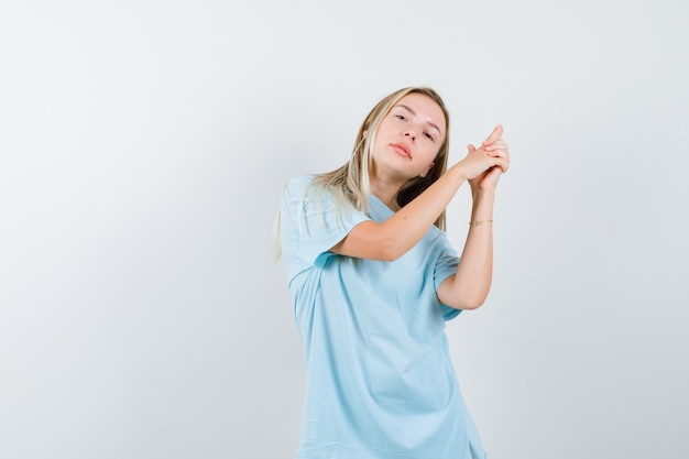 Blond meisje in blauw t-shirt pistool gebaar tonen en op zoek zelfverzekerd, vooraanzicht.