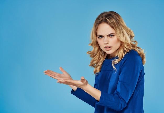 Blond meisje in blauwe jurk emoties charme geïsoleerde achtergrond