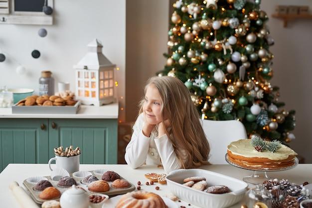 Blond meisje in de keuken van het nieuwe jaar met cupcakes en snoep