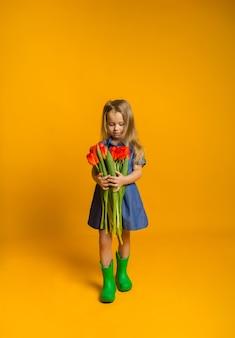 Blond meisje in een blauwe jurk en groene rubberen laarzen staat en kijkt naar een boeket van rode tulpen op een gele achtergrond