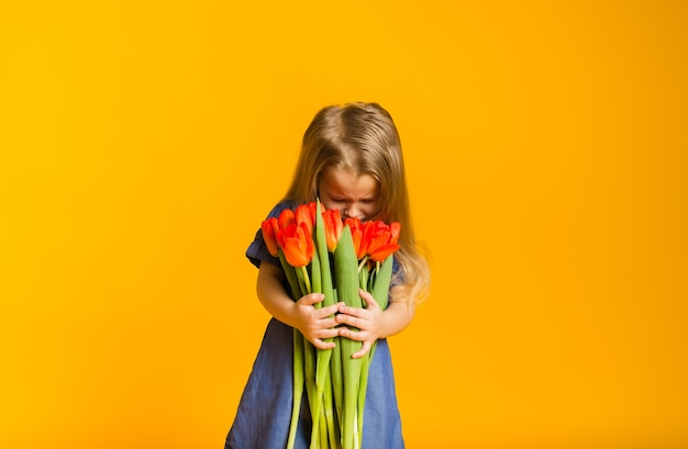 Blond meisje in een blauwe jurk ruikt rode tulpen op een gele muur met een kopie van de ruimte