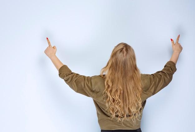 Blond meisje in een groen shirt dat hierboven wijst.