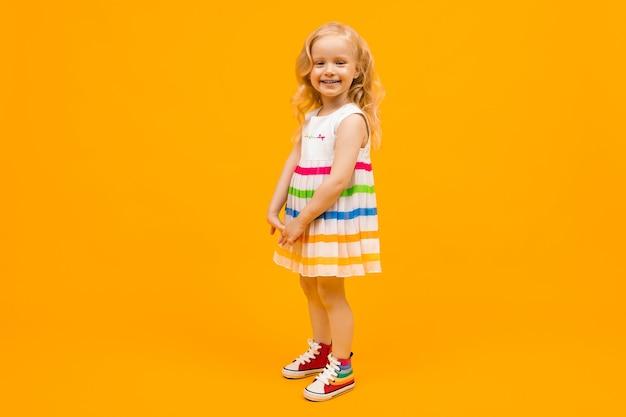 Blond meisje in een heldere gestreepte zomerjurk