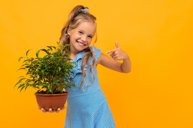 Blond meisje in een jurk heeft een plant op een oranje muur