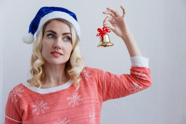 Blond meisje in een kerstmuts met een bel in handen