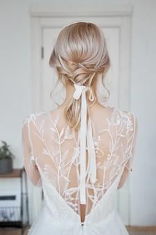Blond meisje in een mooie witte trouwjurk