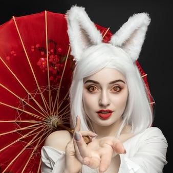 Blond meisje in een pruik op een zwarte achtergrond met een paraplu, cosplay kattenvrouwen.
