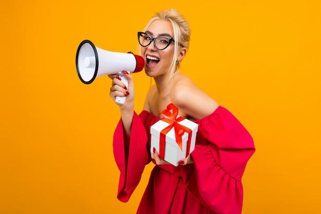 Blond meisje in een rode jurk praat met een megafoon en een geschenkdoos in handen op een gele achtergrond