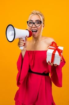 Blond meisje in een rode jurk praat over geschenken met een megafoon en een geschenkdoos in handen op een gele ruimte