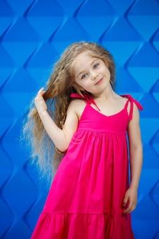 Blond meisje in een roze jurk op een blauwe achtergrond dansen en lachen, heldere kinderemoties van vreugde, gelukkige jeugd
