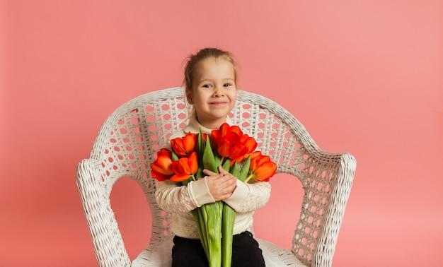 Blond meisje in een witte trui zit op een witte rieten stoel en houdt een boeket rode tulpen op een roze muur