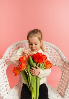 Blond meisje in een witte trui zit op een witte stoel en kijkt naar een boeket rode tulpen op een roze muur