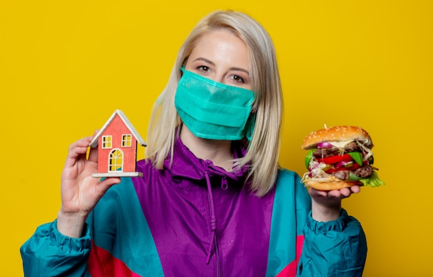 Blond meisje in gezichtsmasker met hamburger en huisje