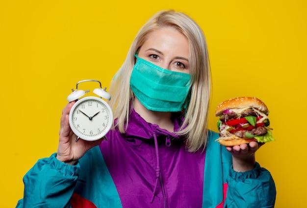 Blond meisje in gezichtsmasker met hamburger en wekker