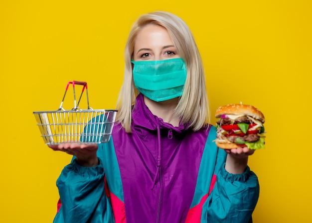 Blond meisje in gezichtsmasker met hamburger en winkelmandje