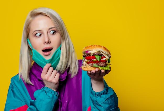 Blond meisje in gezichtsmasker met hamburger