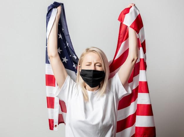 Blond meisje in gezichtsmasker met vlag van de vs.