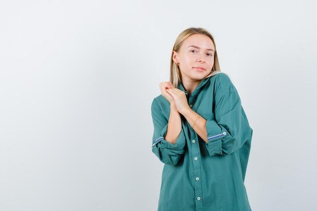 Blond meisje in groene blouse die handen omklemt en er betoverend uitziet