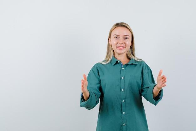Blond meisje in groene blouse die schalengebaar toont en gelukkig kijkt