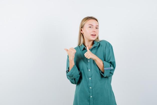 Blond meisje in groene blouse duimen opdagen met beide handen en er mooi uitzien
