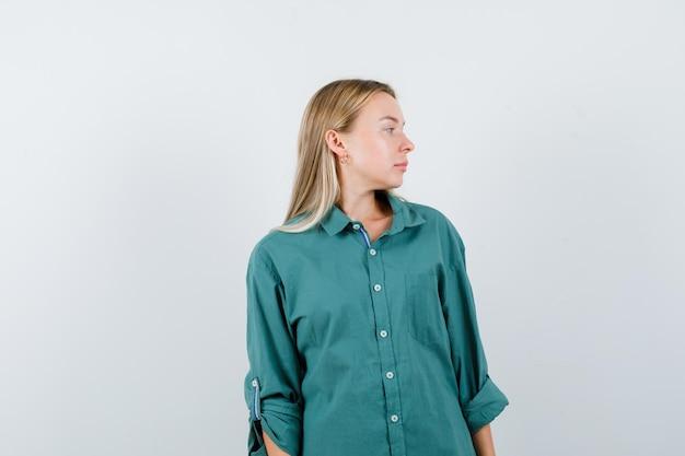 Blond meisje in groene blouse kijkt weg terwijl ze voor de camera poseert en er betoverend uitziet