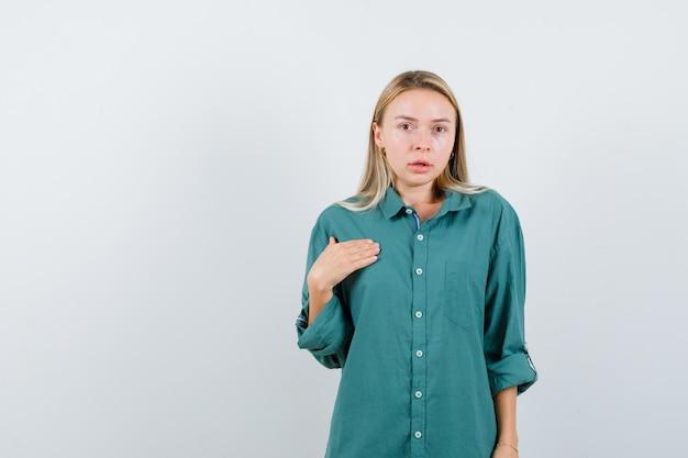 Blond meisje in groene blouse wijst zichzelf en ziet er betoverend uit