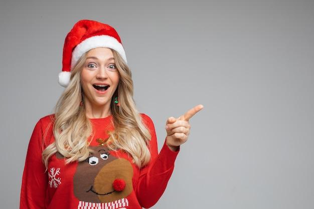 Blond meisje in kerstmuts met lege ruimte met vinger. camera kijken met opwinding en open mond.