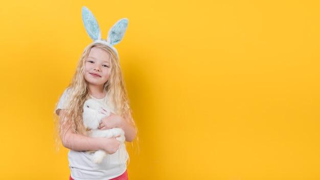 Blond meisje in konijntjesoren met konijn