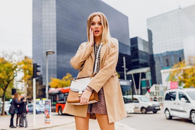 Blond meisje in lente casual outfit buiten wandelen en genieten van vakantie in grote moderne stad. droeg een wollen beige jas en een gestripte blouse. stijlvolle accessoires.