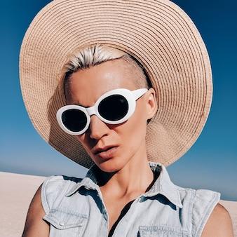 Blond meisje in modeaccessoires. hoed en zonnebril. alleen strandvibes