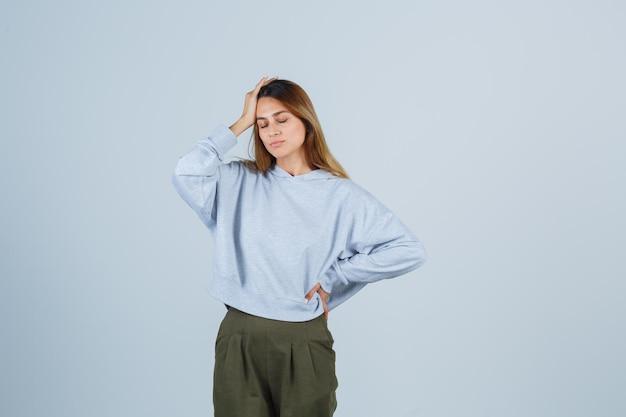 Blond meisje in olijfgroen blauw sweatshirt en broek die een hand op het voorhoofd legt terwijl ze de hand op de taille houdt en er uitgeput uitziet, vooraanzicht.