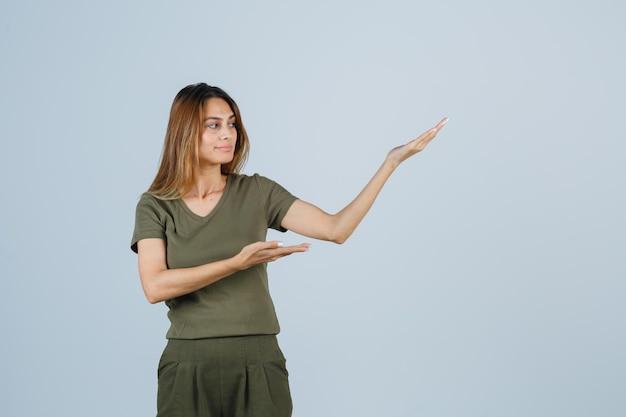 Blond meisje in olijfgroen t-shirt en broek die handen uitrekt terwijl ze iets vasthoudt en presenteert, ernaar kijkt en er gefocust uitziet, vooraanzicht.