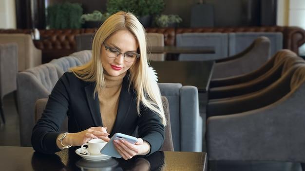 Blond meisje in pak met telefoon zittend aan een tafel in een café, kopieer ruimte
