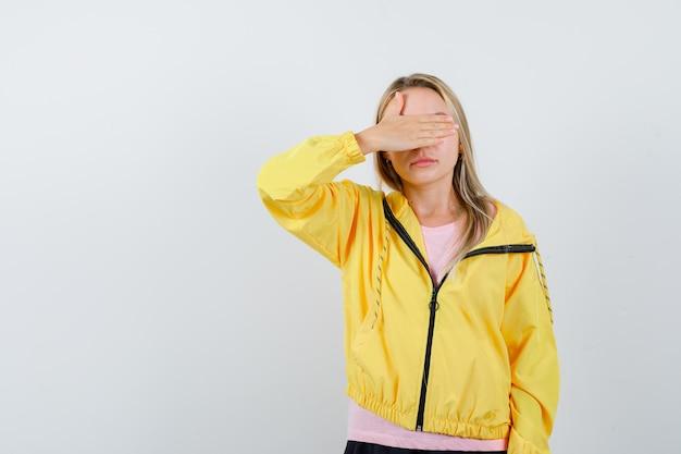 Blond meisje in roze t-shirt en geel jasje dat oog bedekt met hand en er aantrekkelijk uitziet