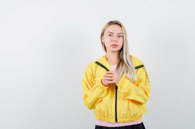 Blond meisje in roze t-shirt en geel jasje handen omklemd en serieus op zoek