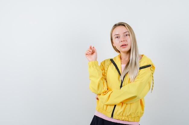 Blond meisje in roze t-shirt en geel jasje verhogen één hand in eureka-gebaar terwijl ze de hand op de elleboog houden en er verleidelijk uitzien