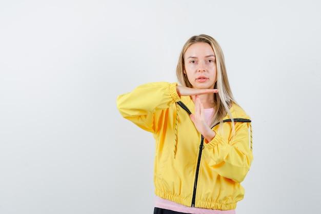 Blond meisje in roze t-shirt en gele jas die een pauzegebaar toont en er serieus uitziet