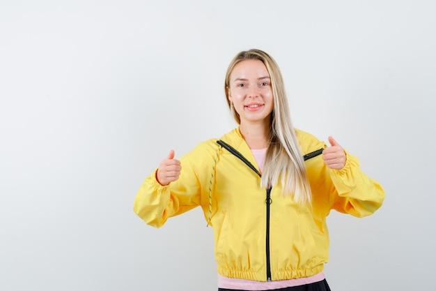 Blond meisje in roze t-shirt en gele jas duimen opdagen met beide handen en tevreden kijken