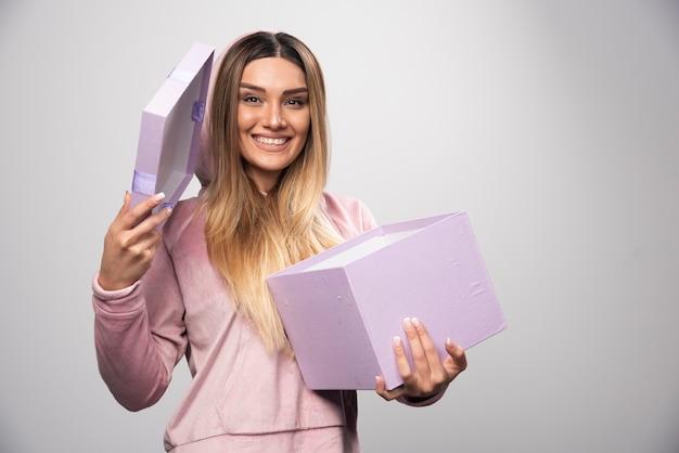 Blond meisje in sweatshirt ontving een geschenkdoos en voelt zich positief verrast.