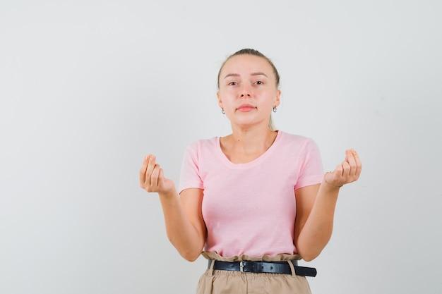 Blond meisje in t-shirt, broek doet geld gebaar, vooraanzicht.