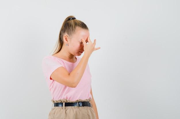 Blond meisje in t-shirt, broek wrijven voorhoofd en op zoek boos, vooraanzicht.